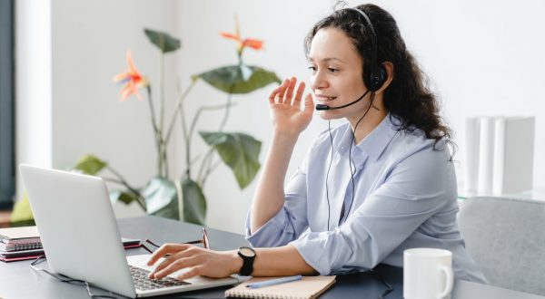 Confident caucasian IT support call center female worker in headset watching conducting webinars online, e-learning, remote teacher tutor working from home on lockdown
