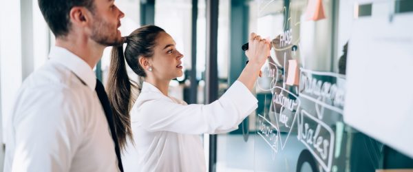 Side view of female drawing scheme of business strategy on glass board while male coworker observing process at modern workplace