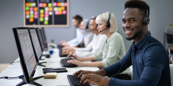 Positive Male Customer Services Agent With Headset Working In A Call Center