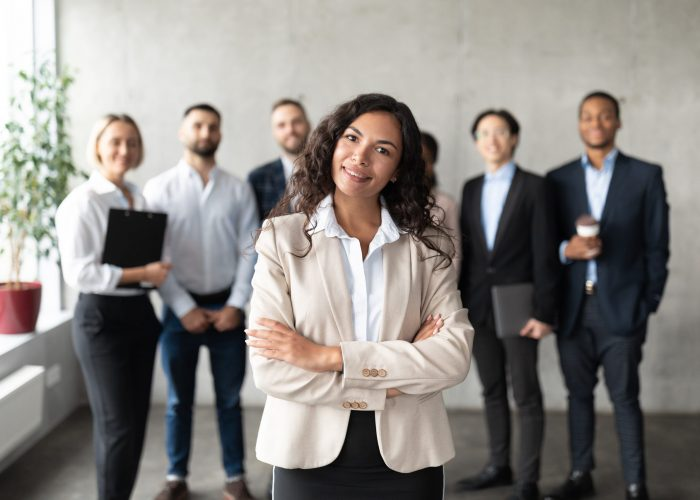 Successful Business Team. Mexican Businesswoman Standing In Front Of Her Employees Smiling To Camera Posing In Modern Office. Female Leadership, Entrepreneurship Career. Selective Focus