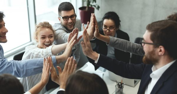 Motivated business team giving group high five, celebrating successful teamwork at meeting