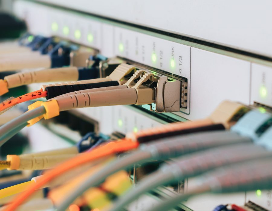 Telecommunications cables are connected to the main server. Internet wires are connected to the central router interfaces. There are many optical patchcards in the data center server room. Selective focus