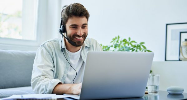 Young man with headset telecommuting